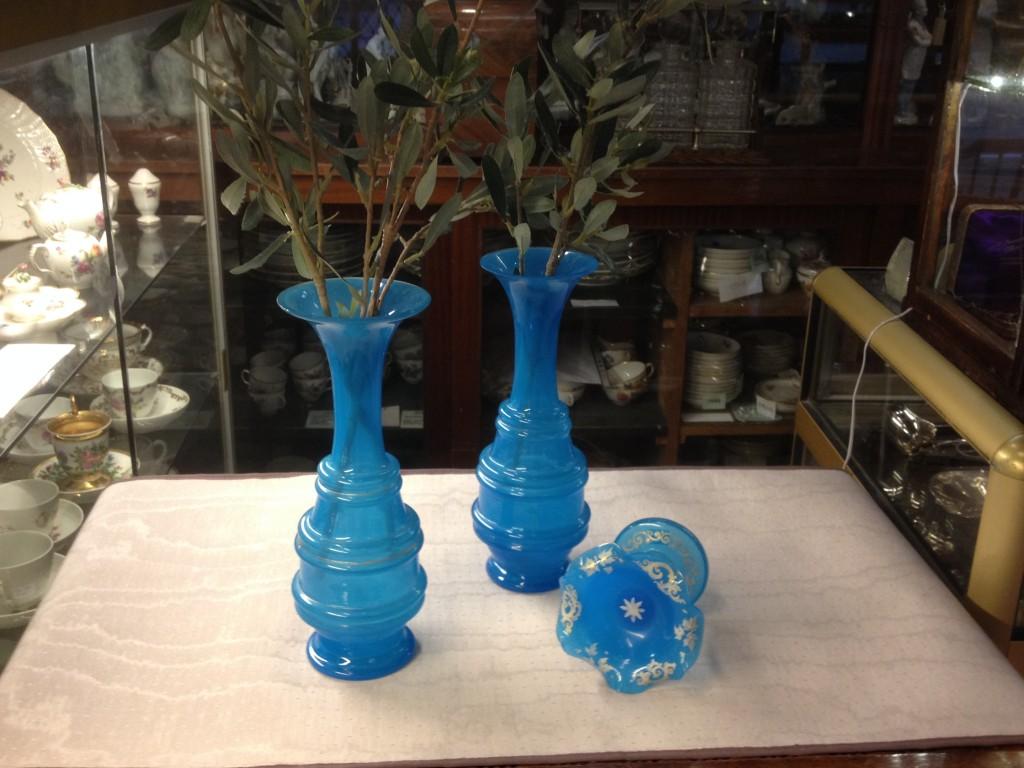 Et par vaser i en skøn turkis farve med en meget diskret gulddekoration. Til højre for vaserne en fin lille opsats i samme skønne farve og med bemaling.